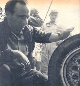 Fangio in foreground examining a tire.  Pirelli personnel in the background.