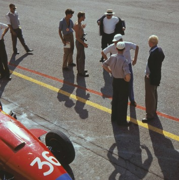Shirtless photographer gets yelled at, for, well, going shirtless. Mike Hawthorn watches on.